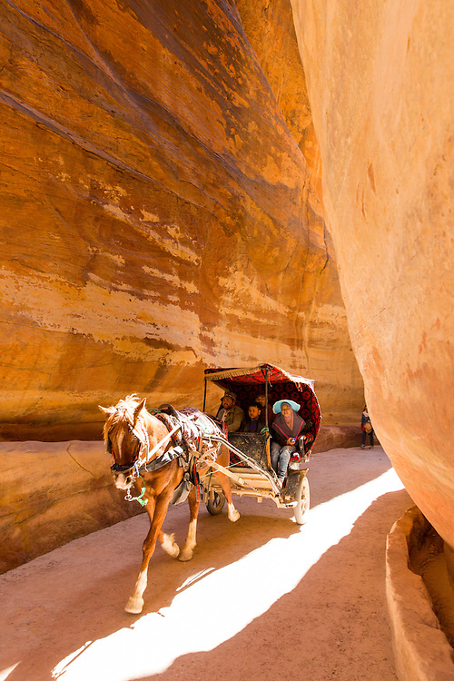 Jordan, Petra, Local horsemen drive carriage for family of tourists on narrow path through canyon leading to ancient ruins