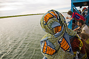 Korioume, Mali 2009 - European travelers and a young girl  from Mali, wrapped head to toe in traditional  colorful wax resist prints,  watches the Niger River slide by from the ferry headed south from Timbuktu. The ferry forms the primary road link to Timbuktu.