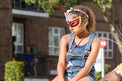 London, August 28th 2016. A girl in a mask watches the passing procession on Ladbroke Grove during Family Day at Europe's biggest street party, the Notting Hill Carnival.