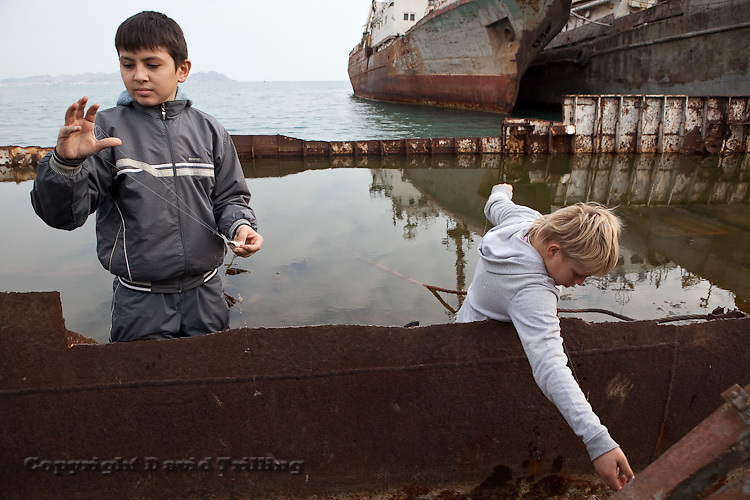 Boys fish from a rusty boat in Turkmenbashi's polluted Caspian Sea harbor.