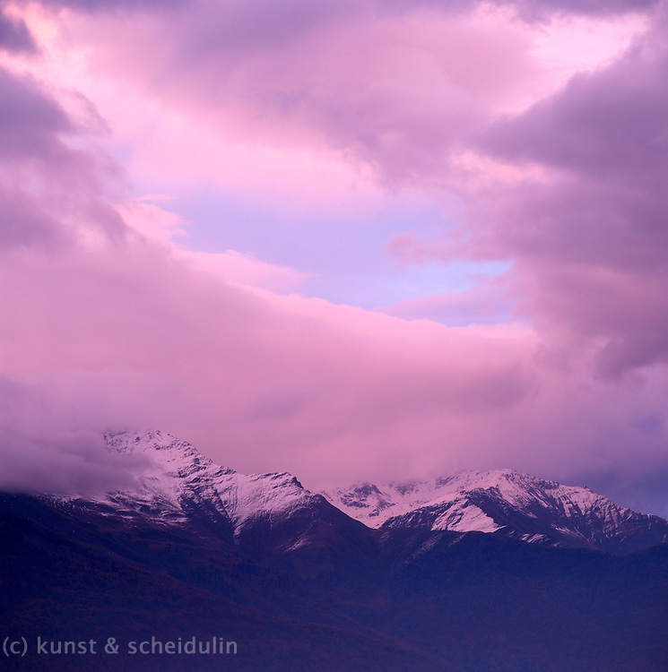 A bit of blue sky is shining through pink clouds over snow-covered mountain peaks. Alps, South Tirol, Italy, Europe.