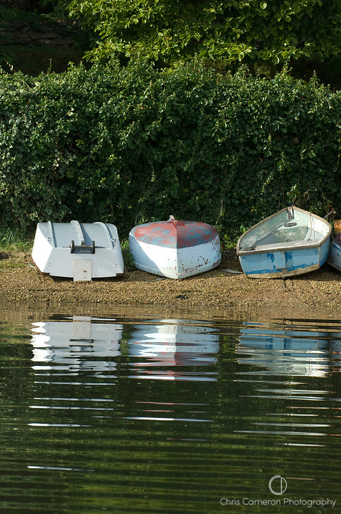 Three dinghies lie on a stoney shore of the Hamble River, Hampshire, England 12/9/2008