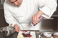 Mid- adult chef puts finishing touches on chocolate cake