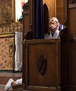 Catholic preiest hearing a confession, Spain.