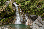 Waterfall at Siberia Hut. The Gillespie Pass Circuit follows the Young and Wilkin Rivers in Mount Aspiring National Park, in the Southern Alps. Makarora, Otago region, South Island of New Zealand. UNESCO lists Mount Aspiring as part of Wahipounamu - South West New Zealand World Heritage Area.