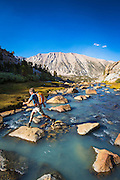Hiker crossing stream in Sam Mack Meadow, John Muir Wilderness, Sierra Nevada Mountains, California