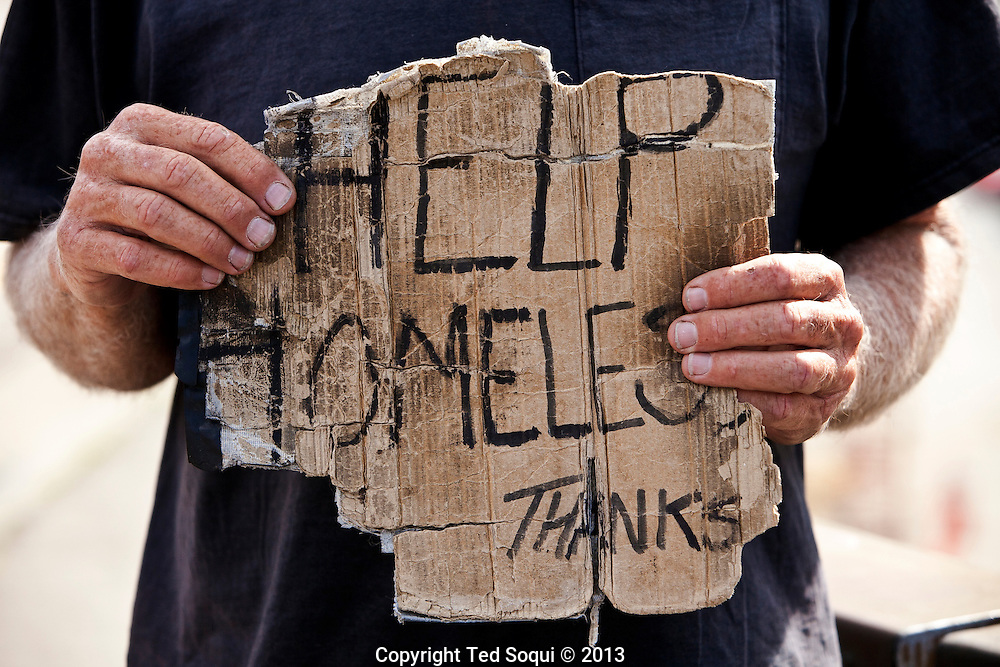 A homeless man holds up his sign in downtown LA.