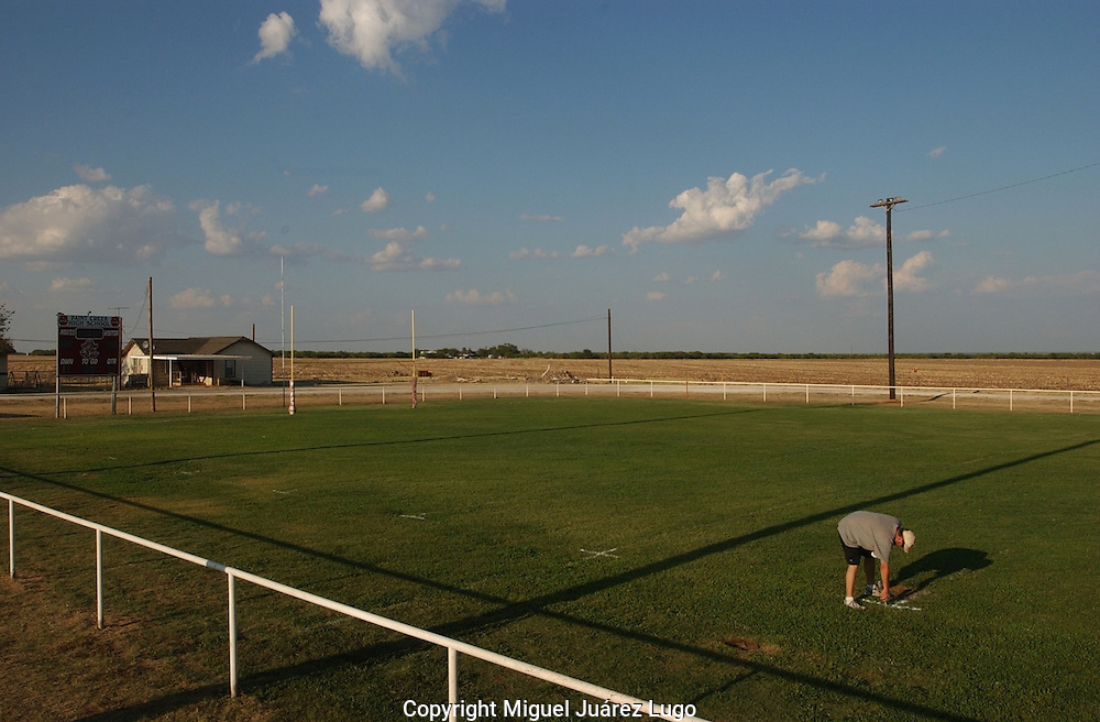 An assistant football coach paints the field just before a Friday night six man football game in Paint Creek, Texas, the hometown of Texas Gov. Rick Perry.  (PHOTO: MIGUEL JUAREZ LUGO).