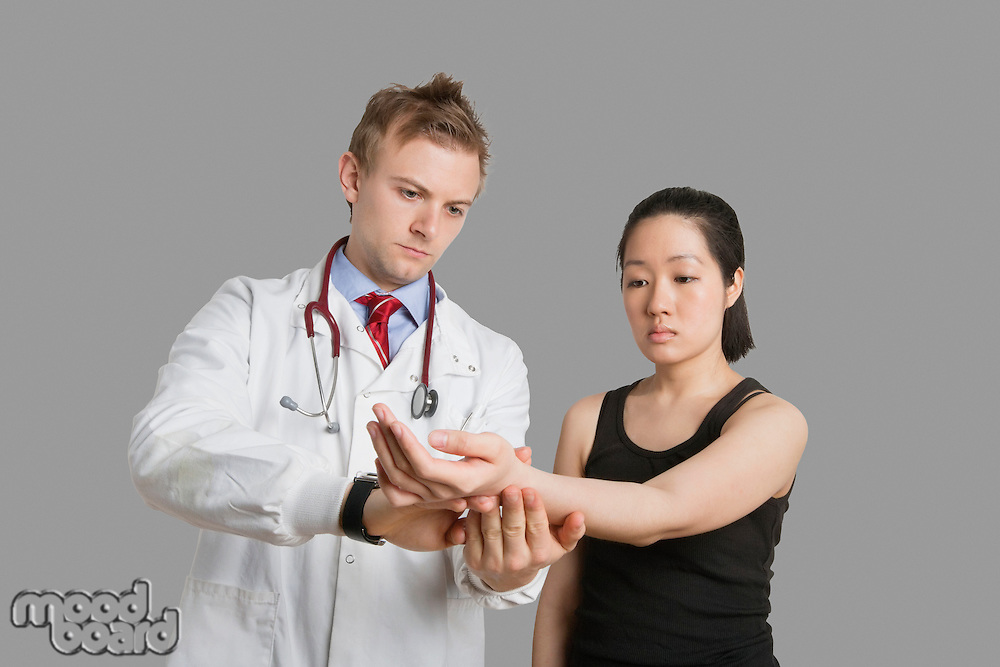 Male doctor checking pulse rate of female patient.