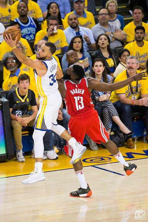 Golden State Warriors guard Stephen Curry (30) battles with Houston Rockets guard James Harden (13) for a loose ball during Game 3 of the Western Conference Finals at Oracle Arena in Oakland, Calif., on May 20, 2018. (Stan Olszewski/Special to S.F. Examiner)