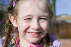 Little girl ; squinting at the sun; smiling,