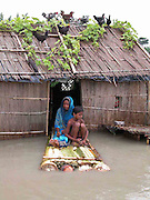 A flood victim family sits in a raft in front of their submerged house as hens perch on the roof at Majher village, about 327 kilometers southwest of Gauhati, the capital city of Northeastern Indian state, Assam, Monday, June 28, 2004. ..Floodwaters of the Asia'a one of the largest river, Brahmaputra and its 35 tributaries have affected more than one million in all of Indian subcontinent and disrupted communication in many parts of the India and Bangladesh, sources said.  (AP Photo/ Shib Shankar Chatterjee)