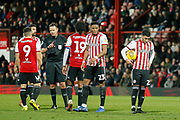 Brentford players argue with the referee after Bolton Wanderers defender David Wheater (31) was booked for a challenge on Brentford attacker Neal Maupay (9) during the EFL Sky Bet Championship match between Brentford and Bolton Wanderers at Griffin Park, London, England on 22 December 2018.
