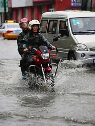 Aug. 3, 2017- Changchun, China -  A motorcycle and a car wade through a waterlogged road in Changchun, northeast China's Jilin Province. Heavy rain has battered Jilin Province since Wednesday evening. Water resources department and meteorological service of Jilin issued a yellow alert for flood. China has a four-tier color-coded weather warning system, with red the most severe, followed by orange, yellow and blue.   (Credit Image: © Lin Hong/Xinhua via ZUMA Wire)