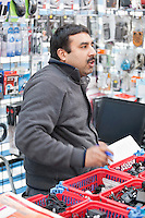 Male sales clerk working in electronics store