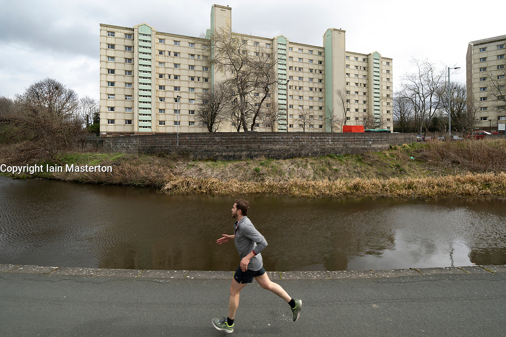 Man running along canal in front of high rise apartment block beside the Union Canal in Wester Hailes, Edinburgh, Scotland, UK