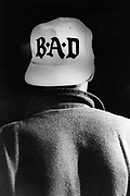 A young person wearing a B.A.D. cap, UK, 1980's.