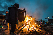 CALAIS, FRANCE - OCT 24: A refugee from Afghanistan holds a wet jumper in front of a fire in the 'jungle' camp in Calais, France on October 24, 2016.