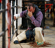 Robert Tucker takes a moment to pray before riding in the bareback competition during the Sokol Park Rodeo Friday, July 20, 2018.  [Staff Photo/Gary Cosby Jr.]