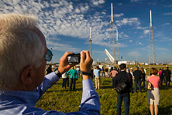 Spectators watching SpaceX Falcon 9 rocket being lifted for launch at Kennedy Space Center.