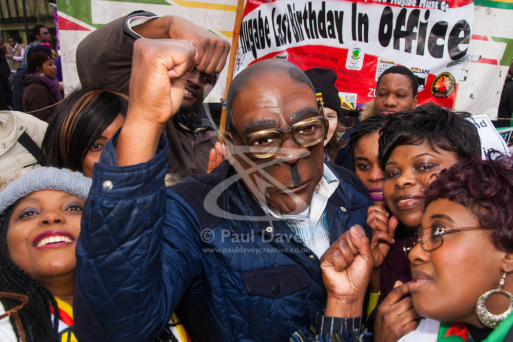 "Lodon, February 21st 2015. Dozens of exiled Zimbabweans gather outside their embassy in London proclaiming Mugabe's last birthday in office. Singing and dancing as they have done every Saturday since 2002, the group spoke with passersby and added yet more names to their petition. PICTURED: ""Mugabe"" makes a black power salute, a familiar gesture by the 91 year old Zimbabwean President whenever he is in the media spotlight."