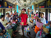 25 NOVEMBER 2017 - YANGON, MYANMAR: A boy sells toys on the Yangon Circular Train. The Yangon Circular Train is a 45.9-kilometre (28.5 mi) 39-station two track loop system connects satellite towns and suburban areas to downtown. The train was built during the British colonial period, the second track was built in 1954. Trains currently run both directions (clockwise and counter-clockwise) around the city. The trains are the least expensive way to get across Yangon and they are very popular with Yangon's working class. About 100,000 people ride the train every day. A a ticket costs 200 Kyat (about .17¢ US) for the entire 28.5 mile loop.    PHOTO BY JACK KURTZ