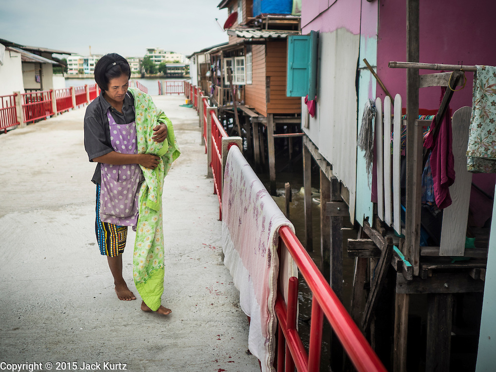 22 JULY 2015 - BANGKOK, THAILAND:   A woman hangs her laundry on a pier on the Chao Phraya River, south of the Krung Thon Bridge.  This is one of the first parts of the riverbank that is scheduled to be redeveloped. The communities along the river don't know what's going to happen when the redevelopment starts. The Chao Phraya promenade is development project of parks, walkways and recreational areas on the Chao Phraya River between Pin Klao and Phra Nang Klao Bridges. The 14 kilometer long promenade will cost approximately 14 billion Baht (407 million US Dollars). The project involves the forced eviction of more than 200 communities of people who live along the river, a dozen riverfront  temples, several schools, and privately-owned piers on both sides of the Chao Phraya River. Construction is scheduled on the project is scheduled to start in early 2016. There has been very little public input on the planned redevelopment.           PHOTO BY JACK KURTZ