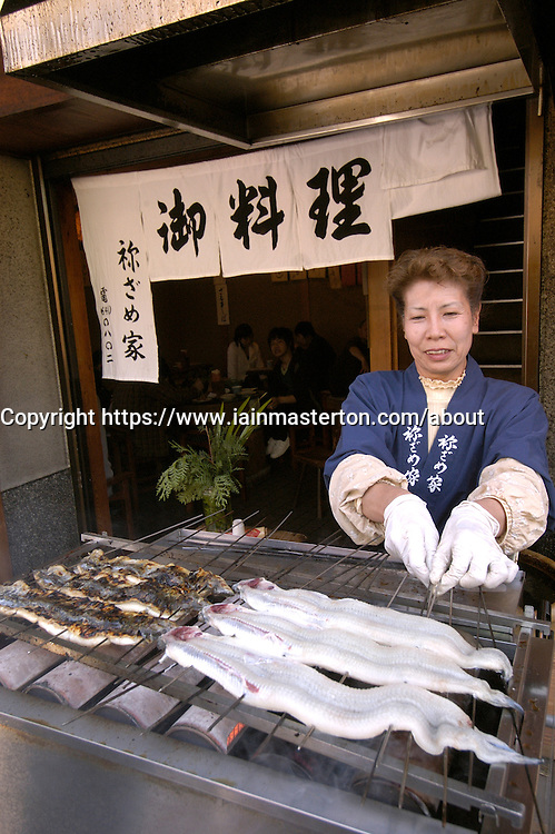 Woman grilling seafood at typical stall outside restaurant in Japan