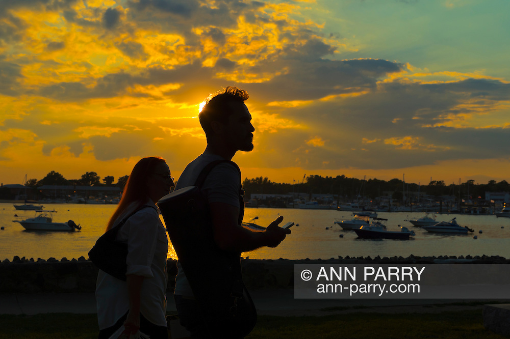 Port Washington, New York, U.S. - July 11, 2014 - As the sun sets, a young man and woman are seen in silhouette as they walk in Sunset Park along Manhasset Bay with boats anchored in water, in the North Shore village on Long Island Gold Coast.