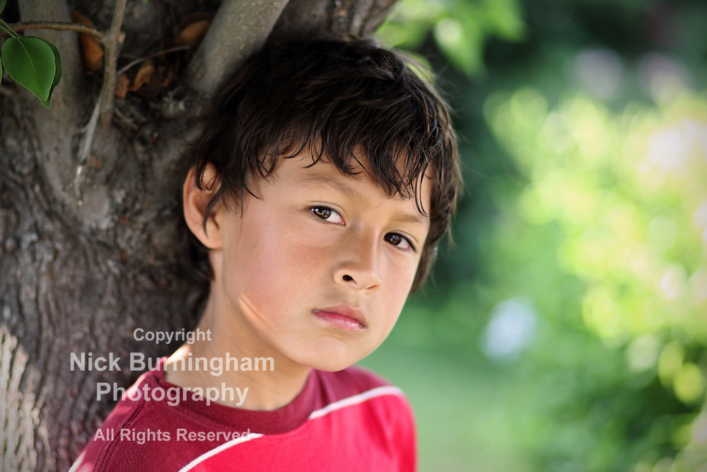 Portrait of hot young boy under a the shade of a tree in summer