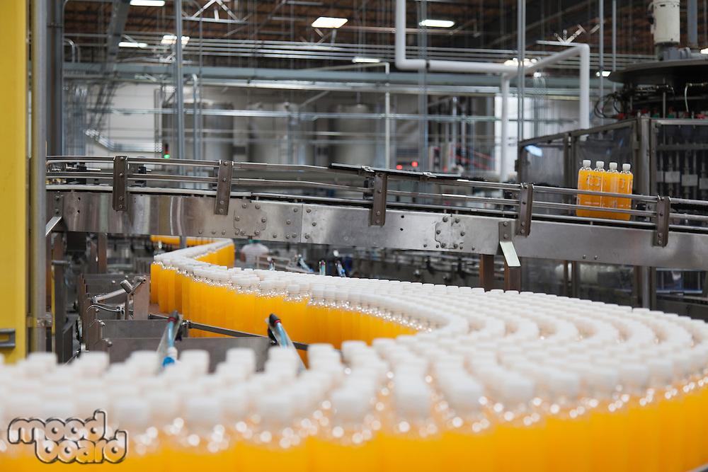 Orange juice bottles on production line