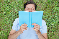 Young man reading book while lying on grass