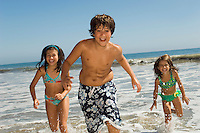 Children in swimwear running through waves