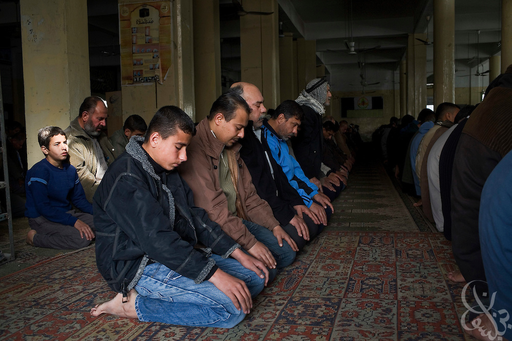 Palestinian men kneel in prayer during Friday services January 16, 2009 in Rafah, Gaza. Residents Rafah are struggling to maintain a sense of normality as the siege by the Israeli forces on Gaza passes day twenty-one. (Photo by Scott Nelson, World Picture Network for the New York Times)..
