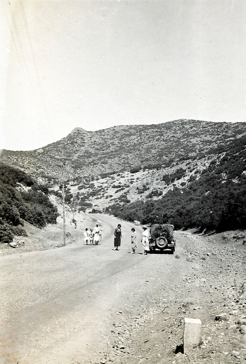 western women with car by the side of the road in mountainous landscape Morocco 1930s