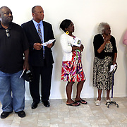 Friends and family listen to remarks Sunday June 22, 2014 during a Cape Fear Habitat for Humanity dedication ceremony of a recently completed home on Tiffany Drive in Wilmington, N.C. (Jason A. Frizzelle)