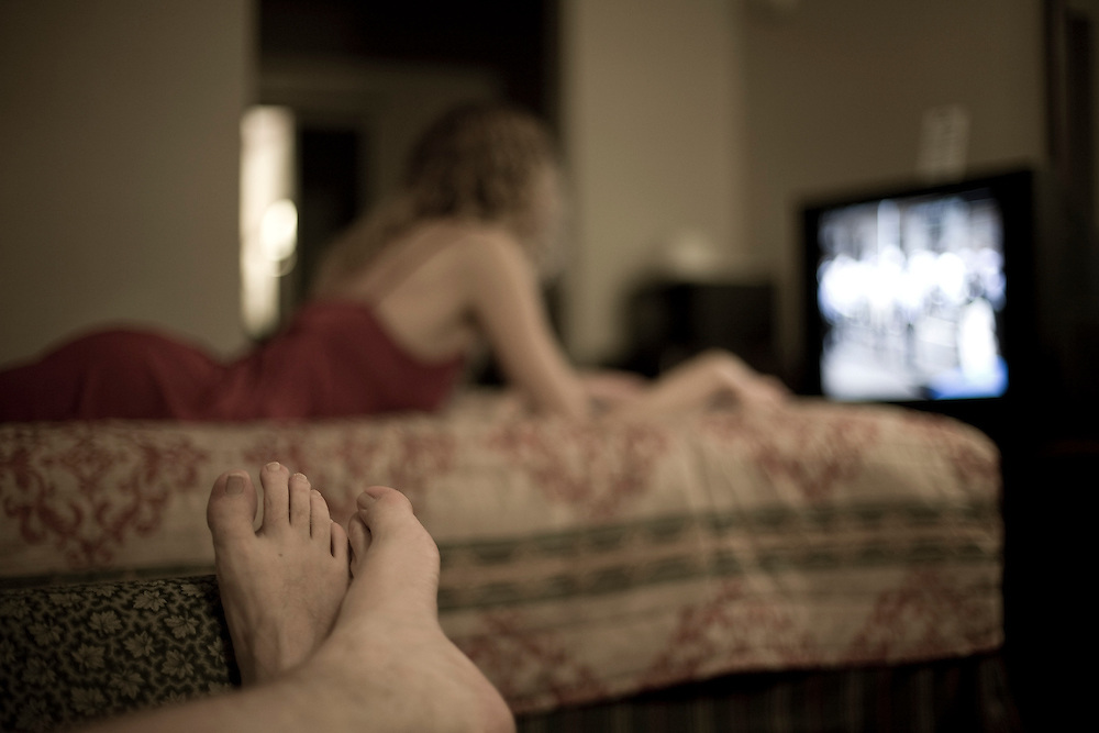 A man lays on a couch in a motel room, feet visible in the foreground. A woman in a red dress lays on the bed in the background watching television.