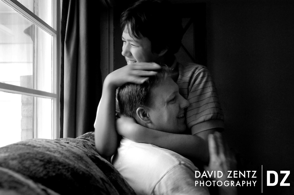 Adam Davis, 12, who is severely autistic, hugs his father Gary Davis at their home in Peoria, Ill. Gary is raising Adam and his 15-year-old daughter Emily, who has Asperger's syndrome, as a single father.
