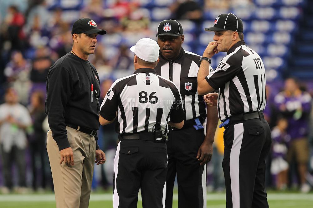Sep 23, 2012; Minneapolis, MN, USA; San Francisco 49ers head coach Jim Harbaugh talks to referees Ken Roan (86), Bill Theodore (117) and Tim Morris (68) prior to the game against the Minnesota Vikings at the Metrodome. Mandatory Credit: Brace Hemmelgarn