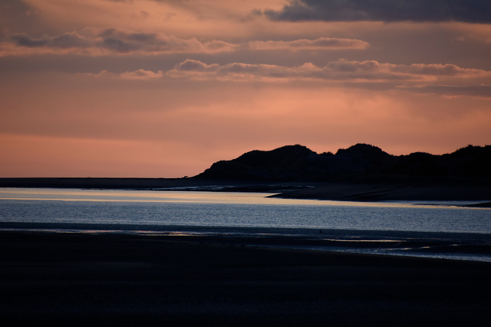 Pink sunset forming on a sandbank between two stretches of water in Raglan, NZ