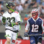 A member of the New York Lizards keeps the ball away from Martin Bowes #12 of the Boston Cannons during the game at Harvard Stadium on July 19, 2014 in Boston, Massachusetts. (Photo by Elan Kawesch)