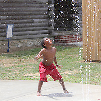 William Moore | BUY at PHOTOS.DJOURNAL.COM<br /> Jaron Jefferson, 6, of Shannon, tries to find the falling water of one of the seven water features at the new splash pad at Shannon City Park.
