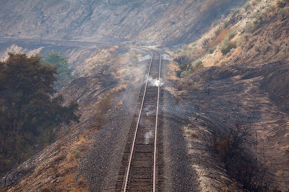Railroad ties smolder in an area burnt by the Chelan Complex Fire in Chelan, Washington August 17, 2015.  The U.S. Army mobilized soldiers on Monday to reinforce civilian fire fighters stretched thin by dozens of major wildfires roaring largely unchecked across the West, with more than 100 homes reduced to ruins in several states.  REUTERS/David Ryder
