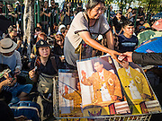 15 OCTOBER 2016 - BANGKOK, THAILAND: A woman sells portraits of Bhumibol Adulyadej, the King of Thailand, on a street in front of the Grand Palace in Bangkok. King Bhumibol Adulyadej died Oct. 13, 2016. He was 88. His death comes after a period of failing health. With the king's death, the world's longest-reigning monarch is Queen Elizabeth II, who ascended to the British throne in 1952. Bhumibol Adulyadej, was born in Cambridge, MA, on 5 December 1927. He was the ninth monarch of Thailand from the Chakri Dynasty and is known as Rama IX. He became King on June 9, 1946 and served as King of Thailand for 70 years, 126 days. He was, at the time of his death, the world's longest-serving head of state and the longest-reigning monarch in Thai history.      PHOTO BY JACK KURTZ