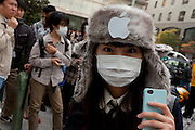 A young woman in a fur hat with an Apple logo on it infront of the lines of people at the Apple store awaiting the official release of the iphone4S in Ginza, Tokyo, Japan. Friday October 14th 2011. The latest version of the popular iphone was released worldwide on October 14th. Japans flagship Apple store in Ginza was opened at 8am for the 800 people that had been waiting to be the first to purchase the new telephone.