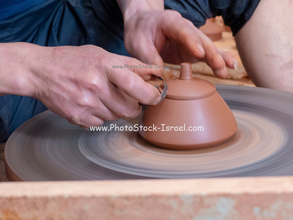 potter in his workshop throws a pot on the potter's wheel in Jianshui, Honghe prefecture, Yunnan province, China.