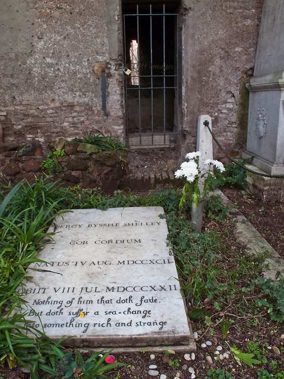 "Shelley grave, Protestant Cemetery, next to a wall with barred window.  Vase of fresh white chrysanthemums next to it.  Inscription clear in the foreground: ""Nothing of him that doth fade but doth suffer a sea-change into something rich and strange."" [ Shakespeare, The Tempest  ]"