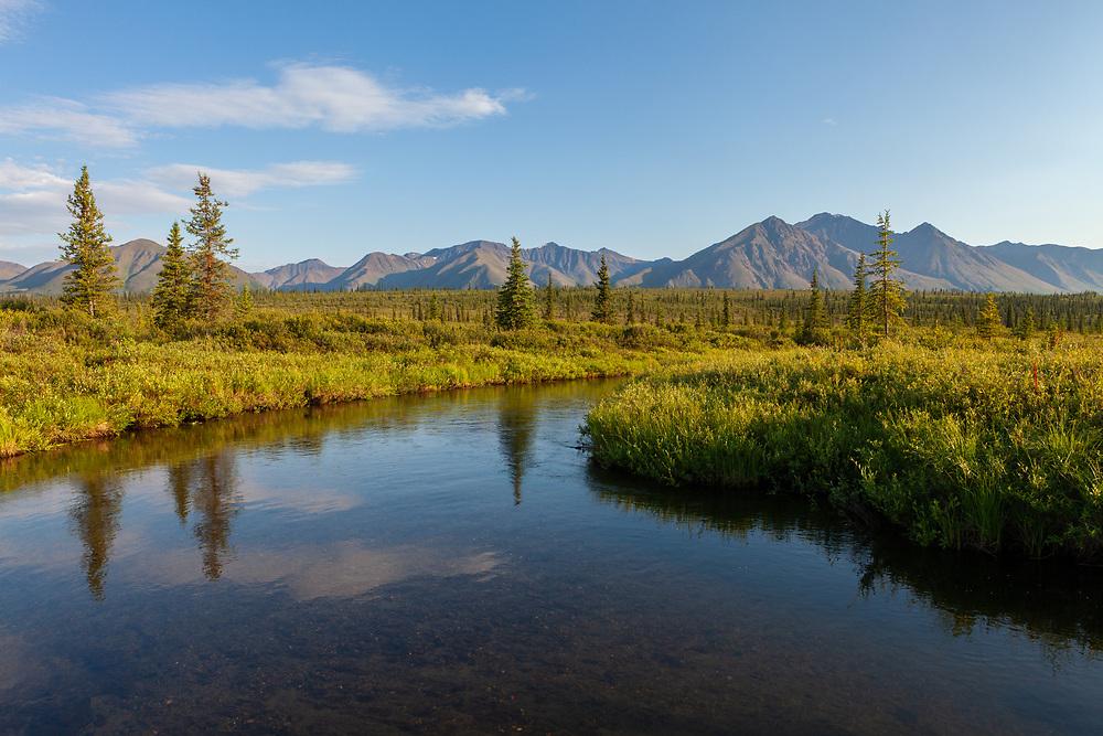 scenic photograph of a small tundra stream with mountain backdrop, interior Alaska