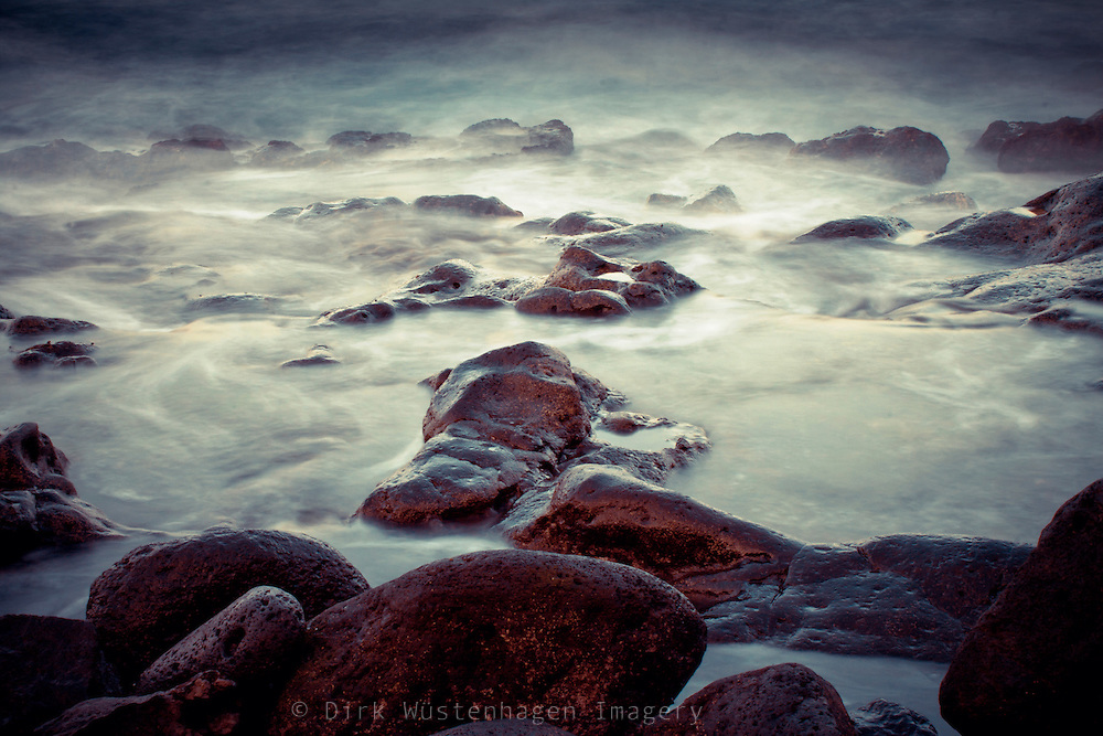 Long exposure of waves spilling over some lava rocks <br />