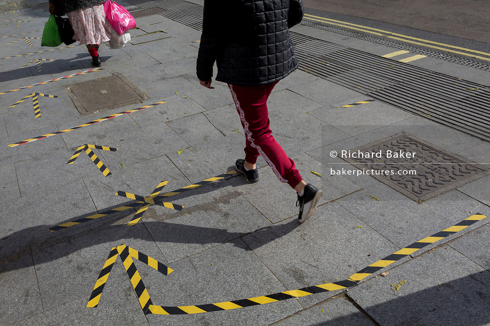 The day after UK Prime Minister Boris Johnson addressed the nation with his roadmap for the coming weeks and months during the Coronavirus pandemic lockdown, south Londoners's feet and legs pass over the now worn hazard tape that marks out safe social distancing practice at East Street Market on the Walworth Road, on 11th May 2020, in London, England.
